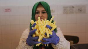 Naisella on siniset kumihanskat ja hänellä on iso kasa ranskalaisia perunoita käsissään.
