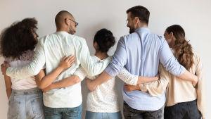 Fme personer, alla med ryggen mot kameran, står på rad och håller om varandra