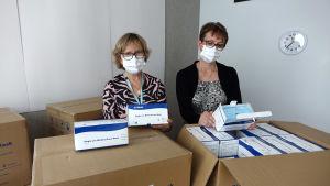 Kymsotesta kotihoidosta palvelualuepäällikkö Kaisa Kelkka ja palveluesimies Kaarina Paju tarkastelevat UPM:n lahjoittamia kasvosuojaimia.