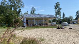 En gul servicebyggnad med omklädningsrum på en strand.