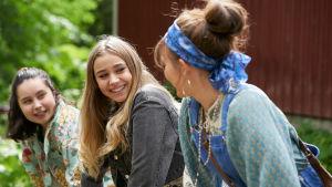 Jenna (Linnea Skog) sitter tillsammans med vänner och de ser glada ut.