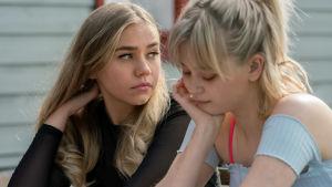 Närbild på Jenna (Linnea Skog) som sitter tillsammans med en annan ung kvinna (Alisa Röyttä).