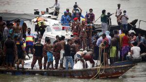 Människor på den båt försöker dra upp andra ur havet