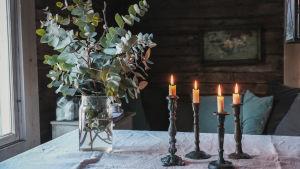 Maljakossa eukalyptuksia, pöydällä kynttilöitä, saunan vilvoittelutila