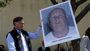 En polis håller upp en bild av Golden State-mördaren Joseph James DeAngelo.