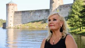 sopraano Karita Mattila istuu Olavinlinnan edustalla