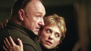 Mies (Gene Hackman) pitelee nuorta naista sylissään, molemmat katsovat sivulle samaan suuntaan.