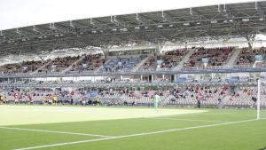 Publik sitter med säkerhetsavstånd på långsidan av Tölö fotbollsstadion.
