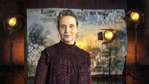Porträttbild av Kirsikka Saari som står i en studio med stuidolampor i bakgrunden.