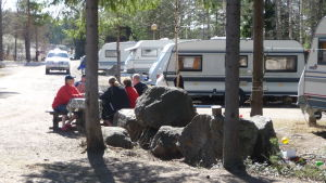 Husvagnar vid en camping och en grupp människor som diskuterar.
