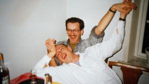 80-90-luku, kaksi silmälasipäistä miestä nauravat ja pitävät toistensa käsistä kiinni.