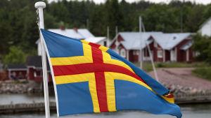 En åländsk flagga i förgrunden, röda hus med vita knutar i bakgrunden.