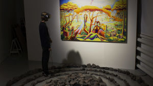 En man testar VR-tekniken. Han står bland med en stenformation. På väggen finns en färggrann tavla.
