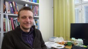En man sitter vid ett skrivbord och ler mot kameran.
