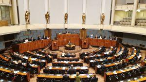 Ett fåtal riksdagsledamöter sitter på sina platser i finska riksdagen och blickar framåt.