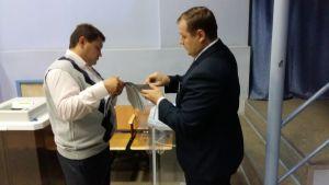 Två män står mittemot varandra i sidoprofil och granskar en bunt papper som den ena mannen håller i sin hand.