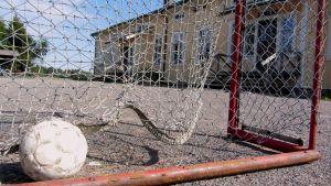 Närbild på en fotboll i ett mål. I bakgrunden syns Haddom skola, en gul byggnad.