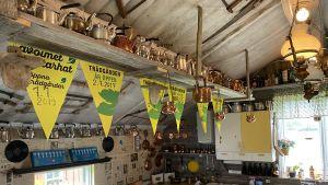 Ett rum med många gamla kaffepannor uppradade längs väggen och på en hylla längs med taket. Gula vimplar hänger i taket.