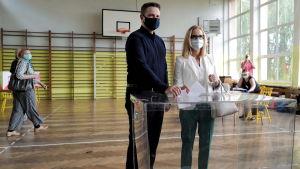En man och en kvinna röstar i en gymnastiksal. Båda har munskydd på sig.