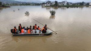 Räddningsarbetare och översvämningsoffer ombord på en båt
