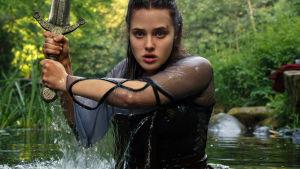 """Katherine Langford i rollen som Nimue i tv-serien """"Cursed"""". På bilden har hon vatten upp till midjan och håller i ett svärd"""