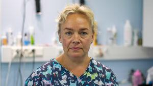 En medelålders blond kvinna som har på sig en blå skjorta med tecknade hundar på.