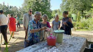 Personer köar för drickbart under trädgårdskonsert.