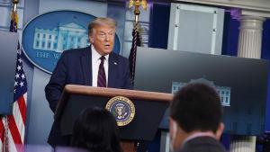 President Donald Trump står vid ett podie framför journalister i Vita huset.