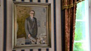Tavla på väggen, föreställer en man med glasögon och grå kostym.