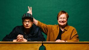"""IMuusikko Iiro Rantala ja presidentti Tarja Halonen istuvat vanhanaikaisessa koulunpulpetissa, Halonen pelleilee ja tekee Rantalan takana """"aasinkorvat""""."""