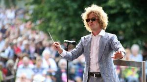Kapellimestari Santtu-Matias Rouvali ohjaa orkesteria aurinkolasit päässä, taustalla näkyy puisto ja yleisöä.