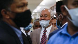 Najib bar sitt munskydd på snedd då han lämnade domstolen i Kuala Lumpur.