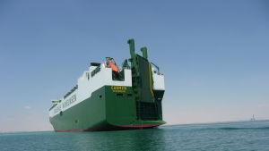 ett grönt fraktfartyg på havet.