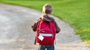 Lapsi kävelee tiellä reppu selässään.