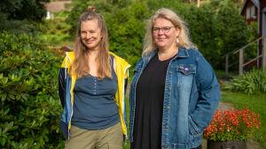 Nora Garusi och Minna Parkkonen poserar i trädgården. De håller båda på med korsstygnsbroderi med feministiskt tema.