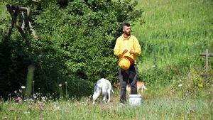 Luca Bianchi tar på sig skyddsdräkten innan han går och ser till sina bikupor. På bilden står han på en äng med hatten i handen och hundarna i bakgrunden.