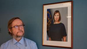 Estlands Helsingforsambassadör Harri Tiido tittar på ett porträtt av den estniska presidenten Kersti Kaljulaid.