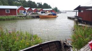 Fagerö i Pyttis, vy ut över havet. Flera röda träbodar vid stranden och en båt vid en brygga.