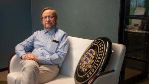 Estlands Helsingforsambassadör Harri Tiidi sitter i en soffa med ambassadens skylt bredvid sig.