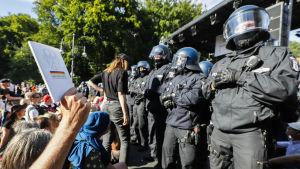 Person håller upp vit bok mot polis i kravallutrustning.