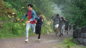Sampo (Amos Brotherus) och de andra deltagarna i skribalägret springer genom ett sommarregn.