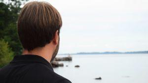 Tomi Ståhlberg står och ser ut mot havet. Han står med ryggen mot kameran. På sig har han en svart pikétröja.