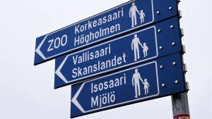 En skylt på vilken det står att man ska gå till vänster för att komma till Mjölö. Skylten är blå, formad som en pil, och texten är vit. Bakgrunden är molnig.