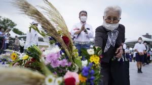 En äldre kvinna lägger blomma för att hedra de 210 000 dödsoffren i Hiroshima och Nagasaki.