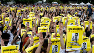 Demonstrerande studenter i Bangkok håller upp bilder på demokratiaktivister som har försvunnit spårlöst efter att ha flytt undan militären till grannlandet Kambodja.