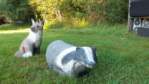 Två djurfigurer som bågskyttar skjuter på i skogen.