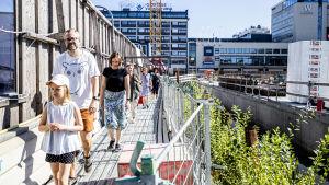 grupp människor som går en rundvandring och tittar på underjordiska parkering som byggs i åbo centrum