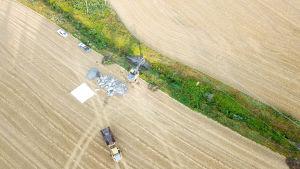 flygbild på grävmaskin på åker