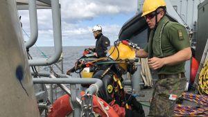 Marinens dykare på väg i vattnet för att utföra oljesaneringsarbete.