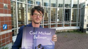 En man står framför Malms kulturhus och håller upp en affisch av pjäsen Bellman 280 år